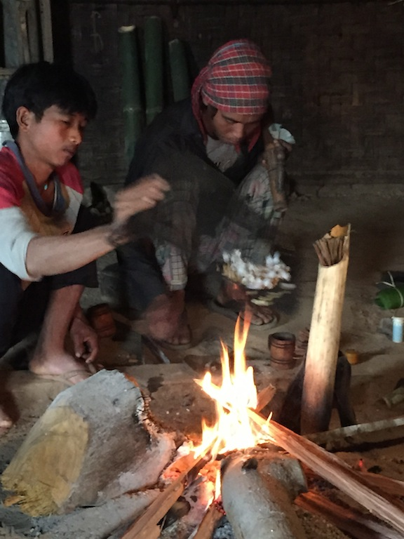 Popping corn over fire. Tea in bamboo pipe.